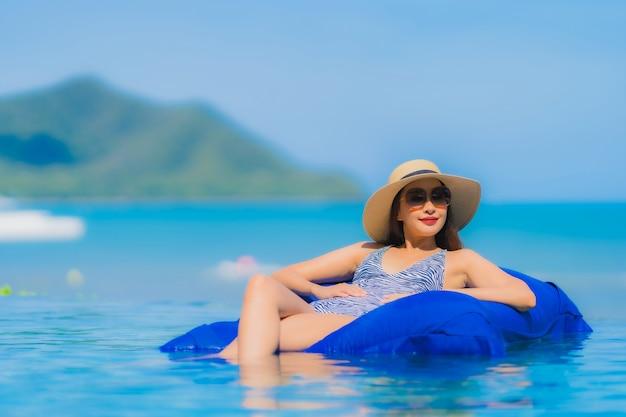 Glückliches lächeln der schönen jungen asiatischen frau des porträts entspannen sich im swimmingpool am neary seeozeanstrand des hotelerholungsortes auf blauem himmel Kostenlose Fotos