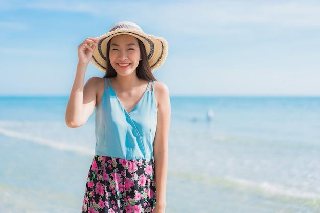 Glückliches lächeln der schönen jungen asiatischen frau des porträts entspannen sich um strandozean und -meer Kostenlose Fotos