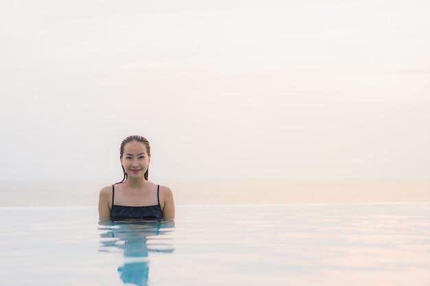 Glückliches lächeln der schönen jungen asiatischen frau des porträts entspannen sich um swimmingpool im hotelerholungsort Kostenlose Fotos