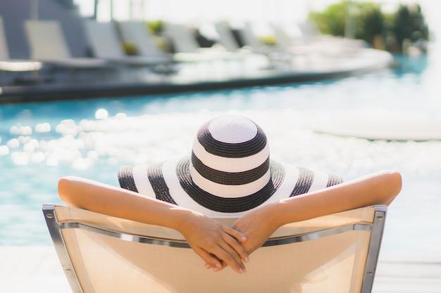 Glückliches lächeln der schönen jungen asiatischen frau des porträts und entspannen sich um swimmingpool im hotelerholungsort Kostenlose Fotos