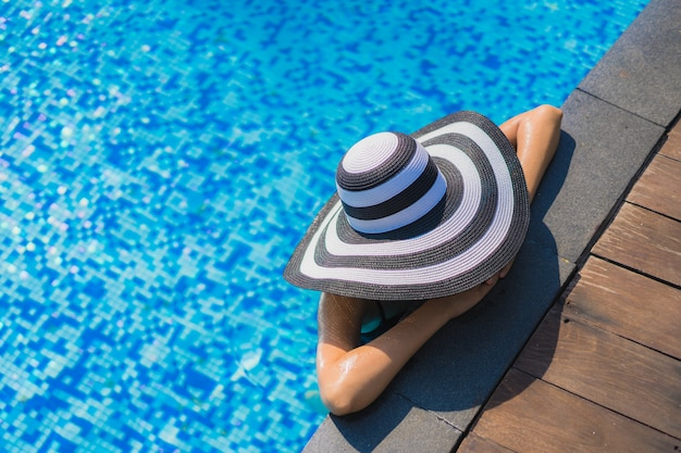 Glückliches lächeln der schönen jungen asiatischen frau und entspannen sich im swimmingpool Kostenlose Fotos