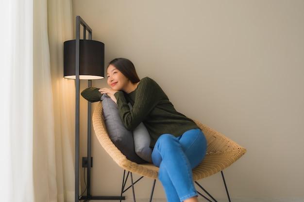 Glückliches lächeln der schönen jungen asiatischen frauen des porträts entspannen sich das sitzen auf sofastuhl Kostenlose Fotos
