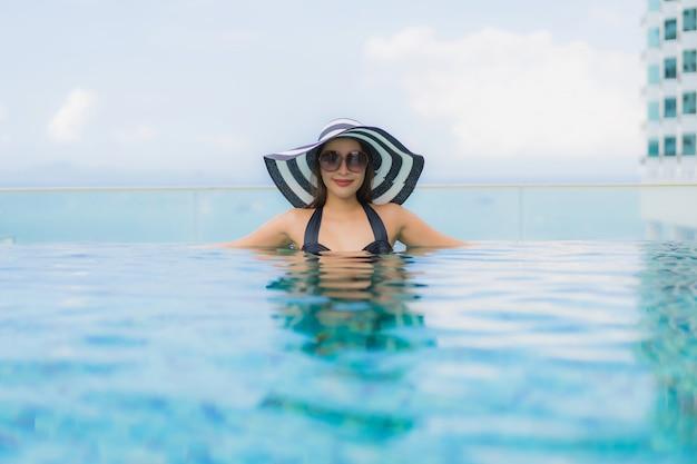 Glückliches lächeln der schönen jungen asiatischen frauen des porträts entspannen sich swimmingpool im freien im erholungsort Kostenlose Fotos