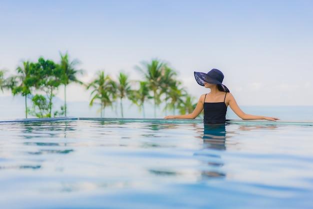 Glückliches lächeln der schönen jungen asiatischen frauen des porträts entspannen sich swimmingpool im freien im hotel Kostenlose Fotos