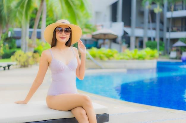 Glückliches lächeln der schönen jungen asiatischen frauen des porträts entspannen sich um swimmingpool im freien Kostenlose Fotos