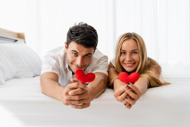 Glückliches lächeln des kaukasischen paarliebhabers und halten des roten herzens in den händen Premium Fotos