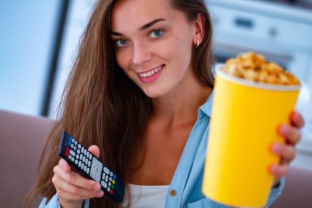Glückliches lächeln frau, die knusprige karamellpopcornbox und fernsehfernbedienung beim fernsehen zu hause hält Premium Fotos