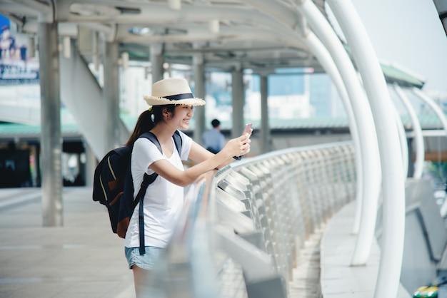 Glückliches lächelndes asiatisches studentenmädchen mit rucksack am stadthintergrund Kostenlose Fotos