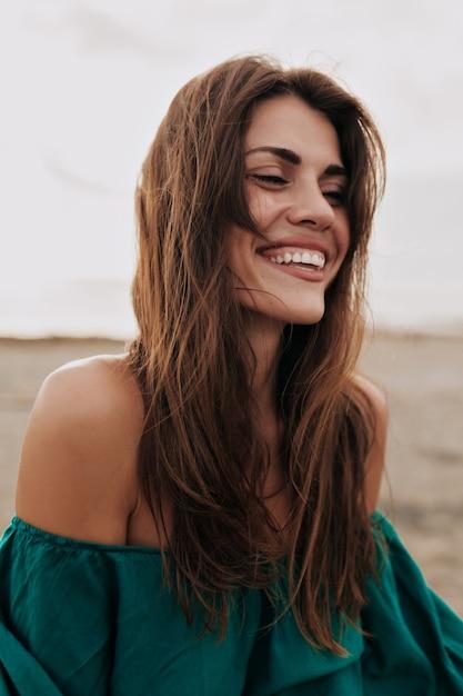 Glückliches lächelndes charmantes modell, das kleid mit nackten schultern trägt, die mit geschlossenen augen am strand lächeln Kostenlose Fotos