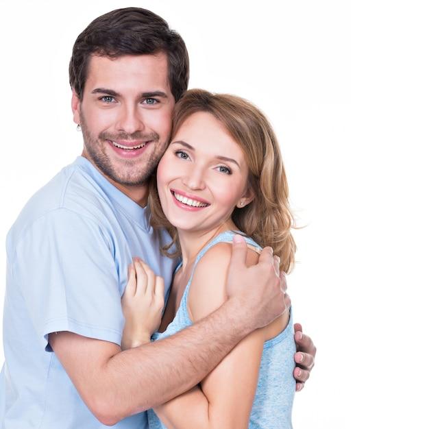 Glückliches lächelndes paar, das zusammen betrachtet kamera betrachtet - lokalisiert Kostenlose Fotos