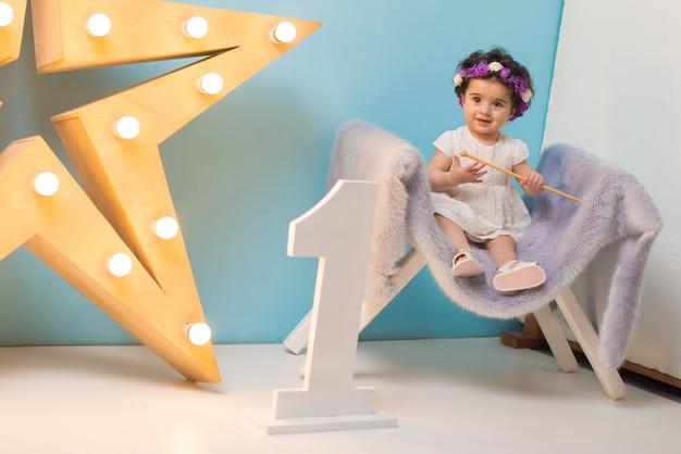 Glückliches lächelndes süßes baby, das auf lehnsessel mit glänzendem hellem stern sitzt Premium Fotos