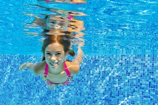 Glückliches lächelndes unterwasserkind im swimmingpool, schönes mädchen schwimmt und hat spaß. kindersport im familiensommerurlaub. aktivurlaub Premium Fotos