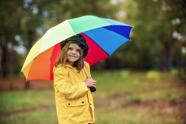 Glückliches lustiges kindermädchen mit mehrfarbenregenschirm in den gummistiefeln am herbstpark Premium Fotos