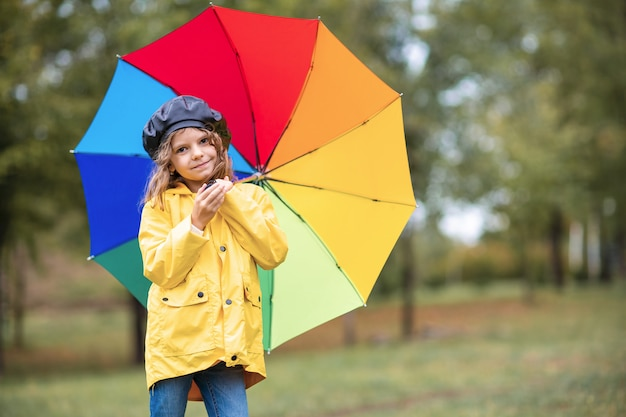 Glückliches lustiges kindermädchen mit regenschirm in den gummistiefeln Premium Fotos