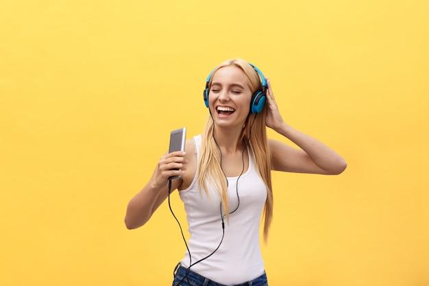Glückliches mädchen, das die musik lokalisiert auf einem gelben hintergrund tanzt und hört Premium Fotos