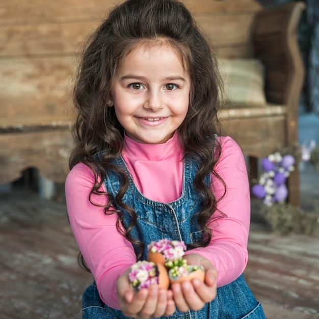 Glückliches mädchen, das gebrochene eier mit blumen hält Kostenlose Fotos