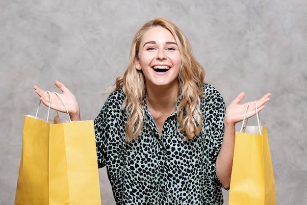 Glückliches mädchen, das gelbe papiertüten hält Kostenlose Fotos