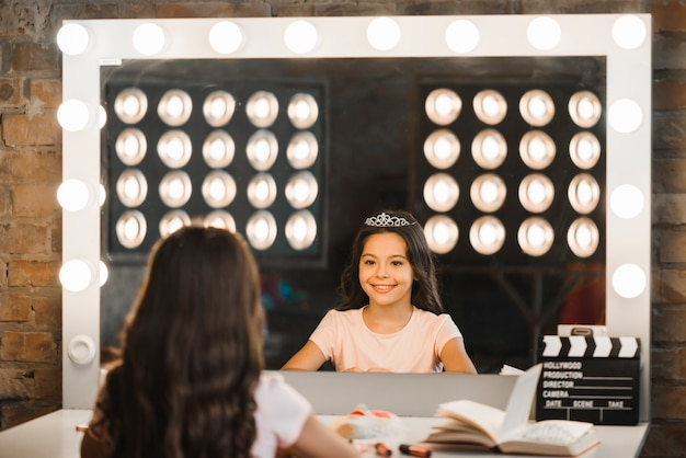 Glückliches mädchen, das ihre reflexion im spiegel an der bühne hinter dem vorhang betrachtet Kostenlose Fotos