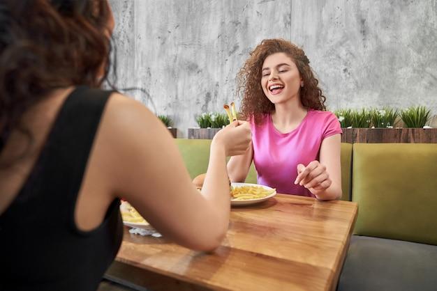 Glückliches mädchen, das im café mit freund sitzt und pommes frites isst. Premium Fotos