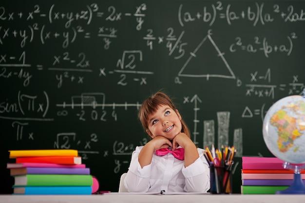 Glückliches mädchen, das im klassenzimmer sitzt und träumt Kostenlose Fotos