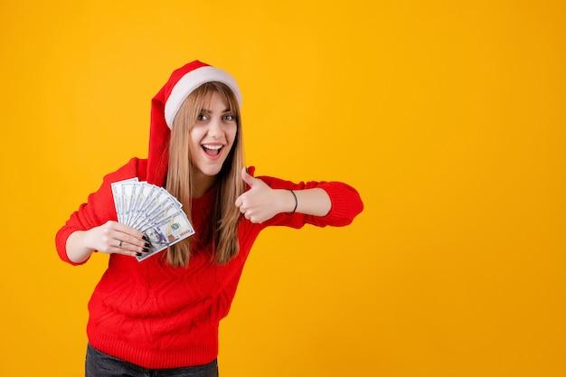 Glückliches mädchen, das in der hand hundert dollarscheine mit den daumen oben tragen sankt-hut hält Premium Fotos