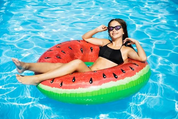 Glückliches mädchen, das in swimmingpool schwimmt Kostenlose Fotos
