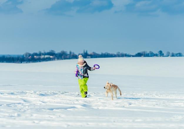 Glückliches mädchen, das mit niedlichem hund im funkelnden schnee läuft Premium Fotos