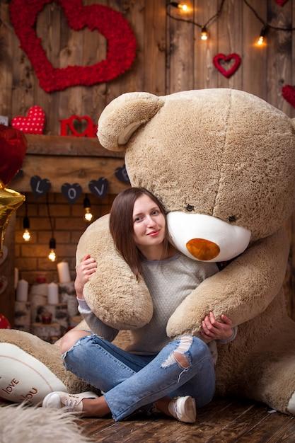 Glückliches mädchen, das mit teddybären in der valentinstagatmosphäre sitzt Premium Fotos