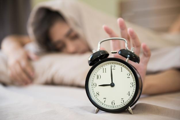 Glückliches mädchen, das morgens aufwacht, den wecker in ihrem schlafzimmer abstellend. Premium Fotos