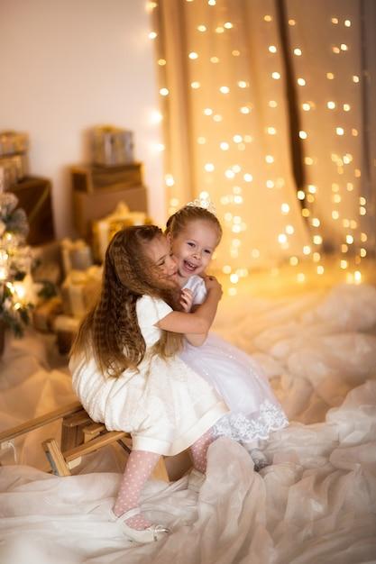 Glückliches mädchen, das nahe dem weihnachtsbaumkonzept frohen weihnachten spielt Premium Fotos
