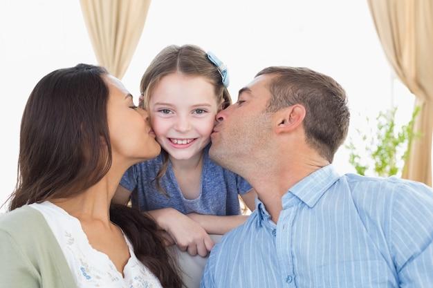 Glückliches mädchen, das von den eltern geküsst wird Premium Fotos