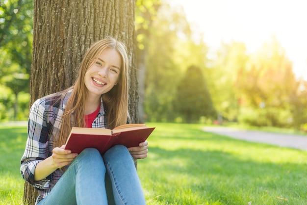 Glückliches mädchen der vorderansicht, das ein buch beim sitzen auf gras liest Kostenlose Fotos