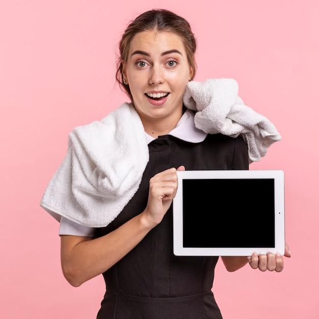 Glückliches mädchen des mittleren schusses, das eine tablette hält Kostenlose Fotos