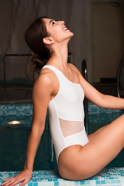 Glückliches mädchen des mittleren schusses mit weißem badeanzug Kostenlose Fotos