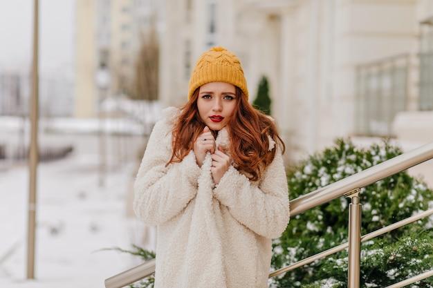 Glückliches mädchen im niedlichen gelben hut, der winter genießt. interessierte dame verbringt dezember tag im freien. Kostenlose Fotos