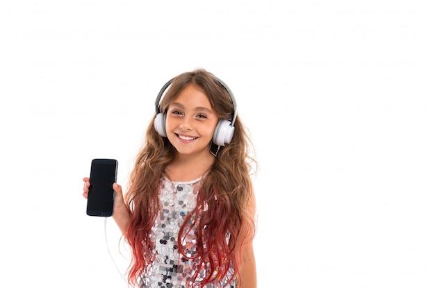 Glückliches mädchen im prickelnden kleid, wenn die großen weißen kopfhörer musik hören und schirm des schwarzen smartphone lokalisiert sind Premium Fotos