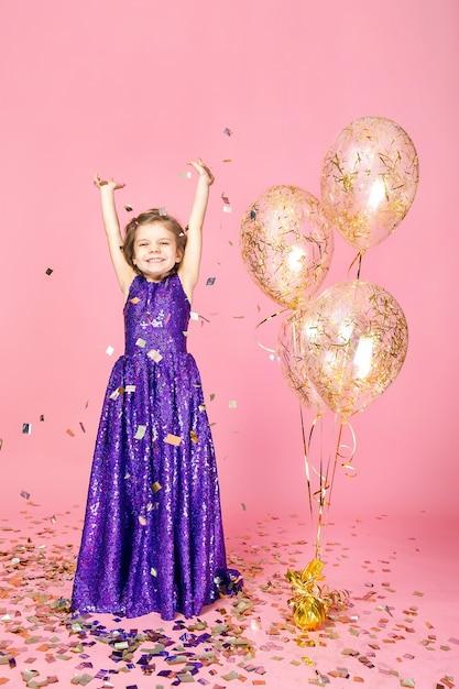 Glückliches mädchen im rosa kleid feiernd Premium Fotos