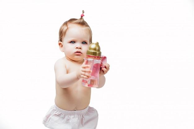 Glückliches mädchen in der windel hält flasche milchhandnahrungslebensmittel und -getränk für neugeborenes raster mit dem kleinen kind, das auf weiß lokalisiert wird. Premium Fotos