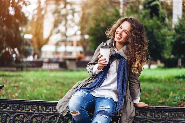 Glückliches mädchen mit dem lockigen haar genießen das im freiengetränk Premium Fotos