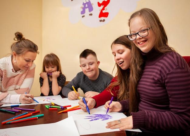 Glückliches mädchen mit down-syndrom, das beim zeichnen aufwirft Kostenlose Fotos