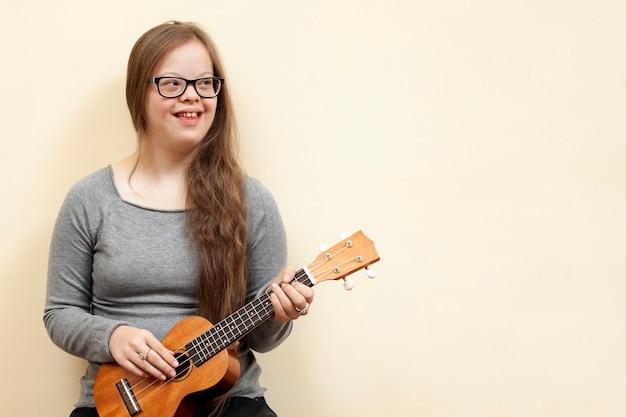 Glückliches mädchen mit down-syndrom, das gitarre hält Kostenlose Fotos
