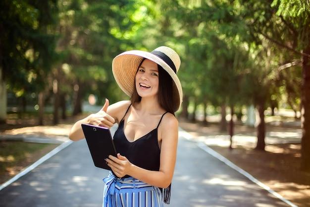 Glückliches mädchen mit einer tablette in der hand und einem hut, einem geschäft und einer sozialen tätigkeit im internet tragend, die in der natur sind. Premium Fotos