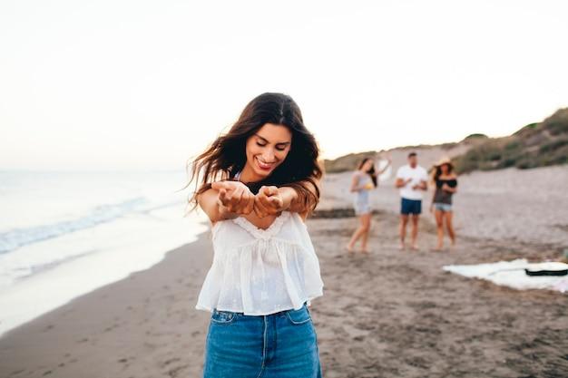 Glückliches mädchen mit ihren freunden am strand Kostenlose Fotos