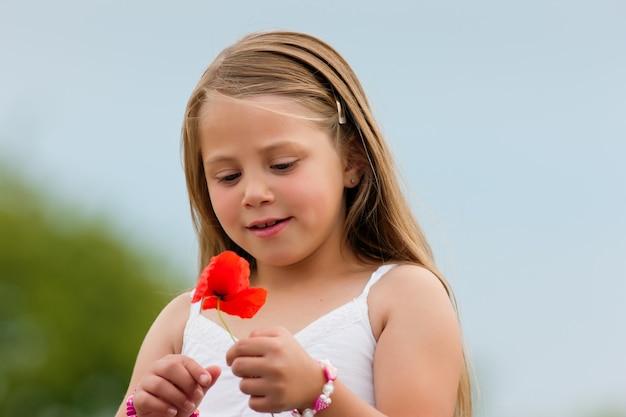 Glückliches mädchen mit mohnblume Premium Fotos