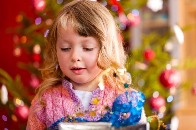 Glückliches mädchen mit weihnachtsgeschenk am heiligabend Premium Fotos