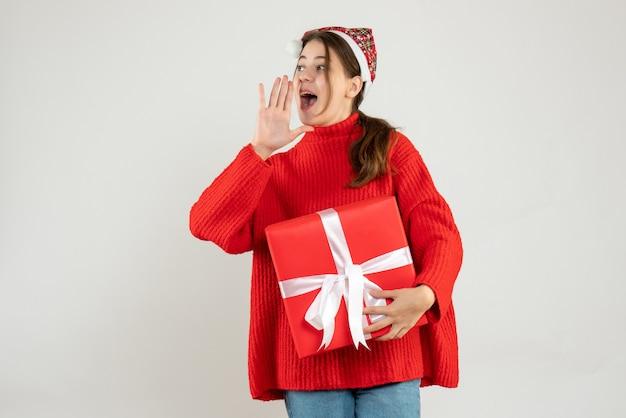 Glückliches mädchen mit weihnachtsmütze, das geschenk hält, das jemanden auf weiß anruft Kostenlose Fotos