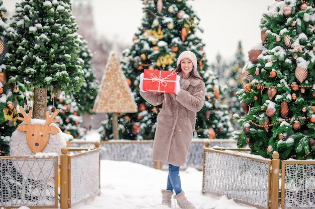 Glückliches mädchen nahe tannenbaumast im schnee für neues jahr. Premium Fotos