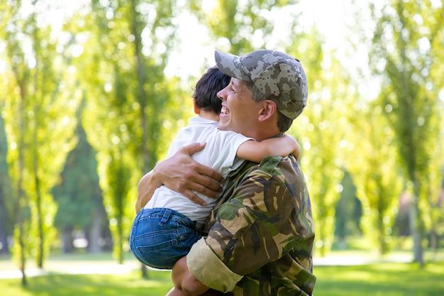 Glückliches militärisches vatertreffen mit kleinem sohn nach missionsreise, jungen in den armen haltend und lächelnd. familientreffen oder rückkehr nach hause konzept Kostenlose Fotos