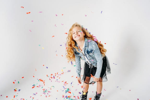 Glückliches modern gekleidetes tweenmädchen des gelockten haares herein in der denimjacke und im schwarzen ballettröckchenrock und in den rauen stiefeln auf weiß mit bunten konfettis Premium Fotos
