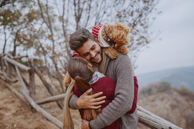 Glückliches multikulturelles paar in der liebe gekleidet lässig umarmend in der natur im herbst. mann, der ihren hund auf den schultern hat. Premium Fotos
